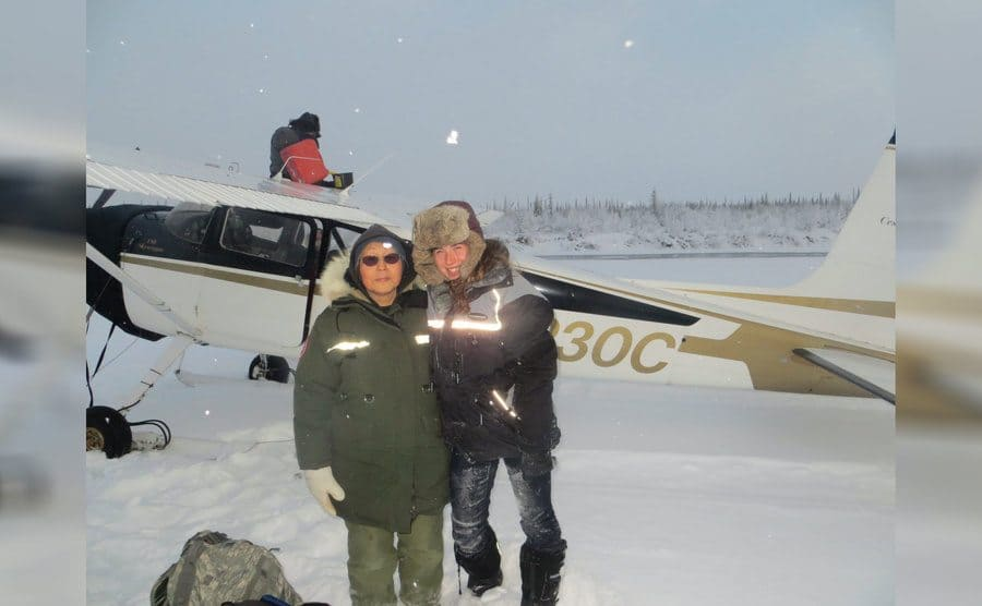 Edna Rose and Aidan in front of their small plane surrounded by snow