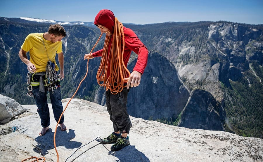 Tommy Caldwell and Alex Honnold at the top of a mountain with a lot of rope