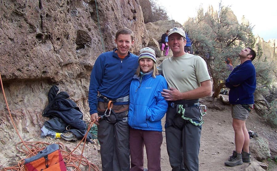 Tommy, Beth, and Lee standing at the bottom of the cliff with their gear on
