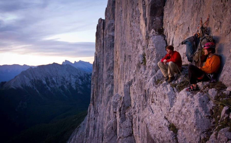 Tommy Caldwell and another climber resting on a small ledge in the cliff