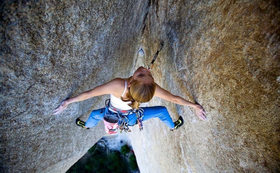 Beth Rodden climbing between two large rocks