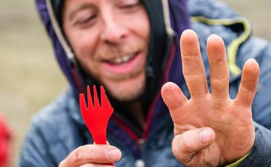 Tommy Caldwell holding up a plastic fork with a knife built into it next to his missing finger