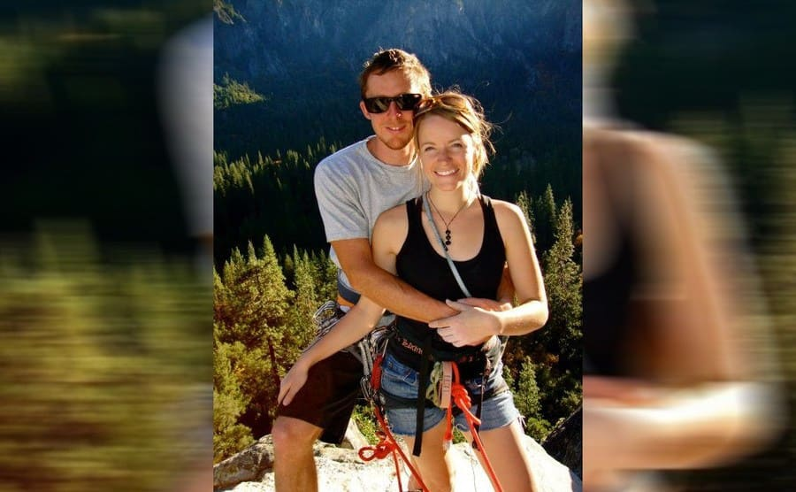 Tommy Caldwell and Beth Rodden in climbing gear posing for a photograph with a large drop behind them