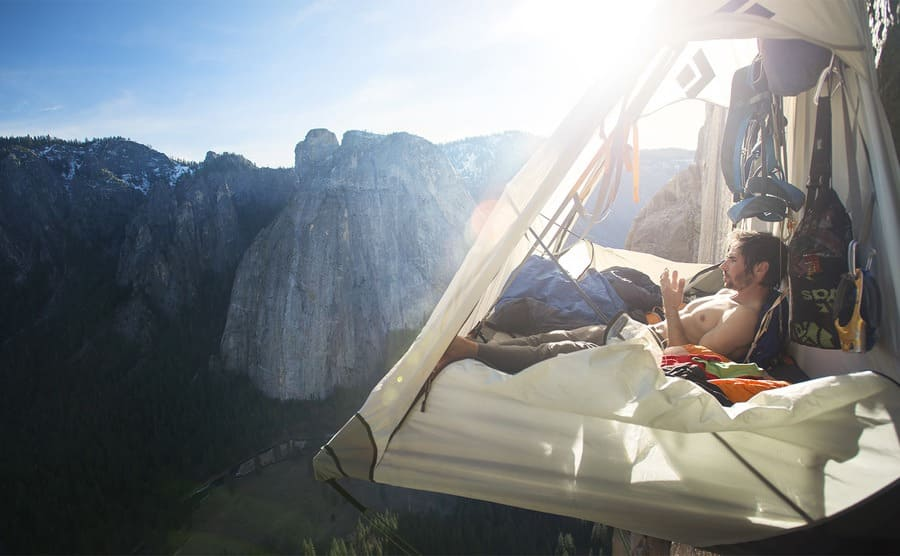 Kevin Jorgeson resting in a tent which is hanging from a hook on the side of the El Captain's Dawn Wall