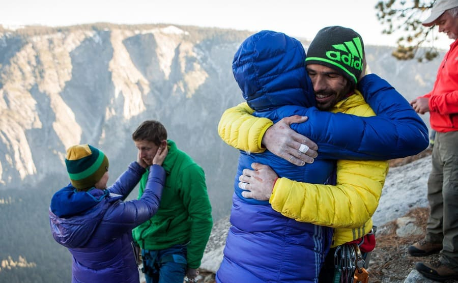 Tommy and Kevin hugging their loved ones at the top of the wall