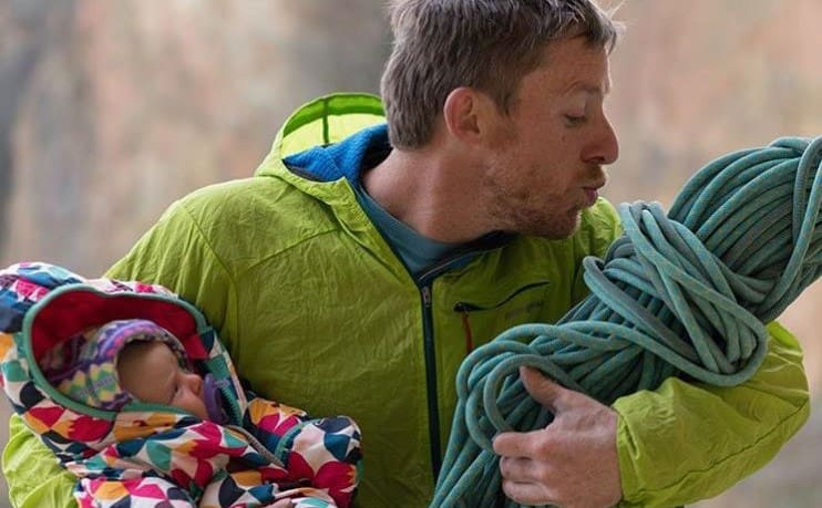 Tommy Caldwell holding his baby in one arm and rope balled up in the shape of a wrapped baby while he pretends to give a kiss to the rope