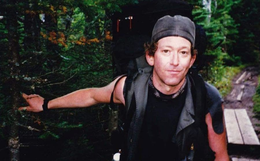 Baltimore Jack with his hiking gear taking a photograph on a woodsy path while holding a tree