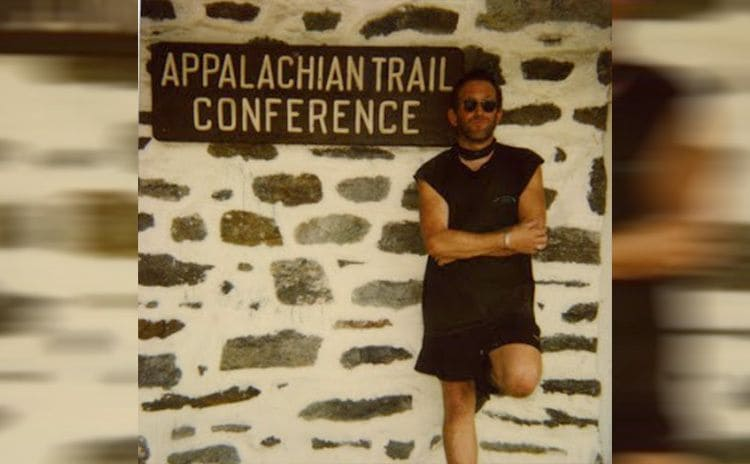 Baltimore Jack leaning against a stone wall with a sign for the Appalachian trail conference behind him