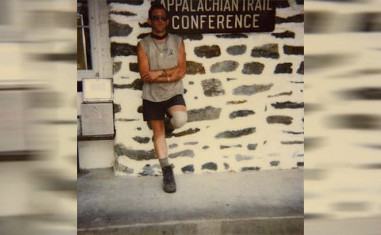 A photograph of Baltimore Jack leaning against the Appalachian trail conference sign in 1999