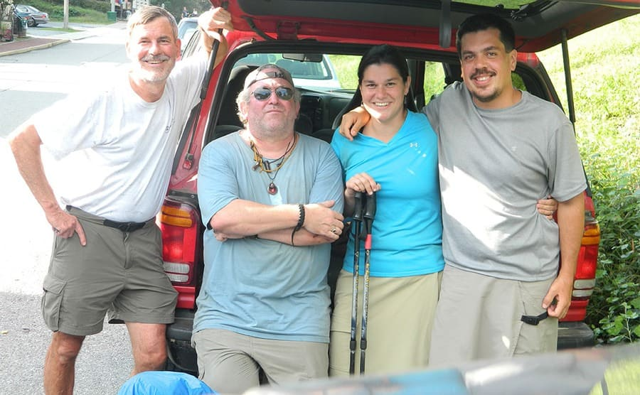 Baltimore Jack with other hikers posing behind a red Jeep