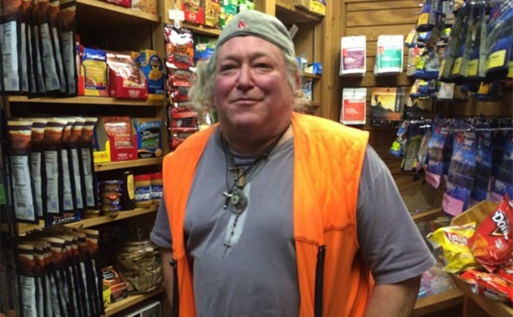 Baltimore Jack standing in a kiosk with snacks around him