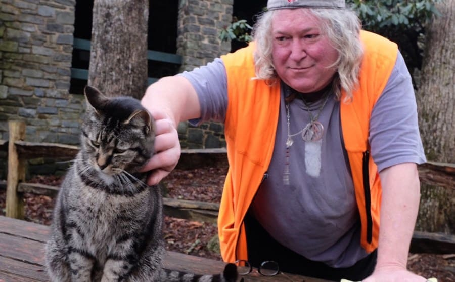 Baltimore Jack petting a cat that is sitting on a wooden picnic table