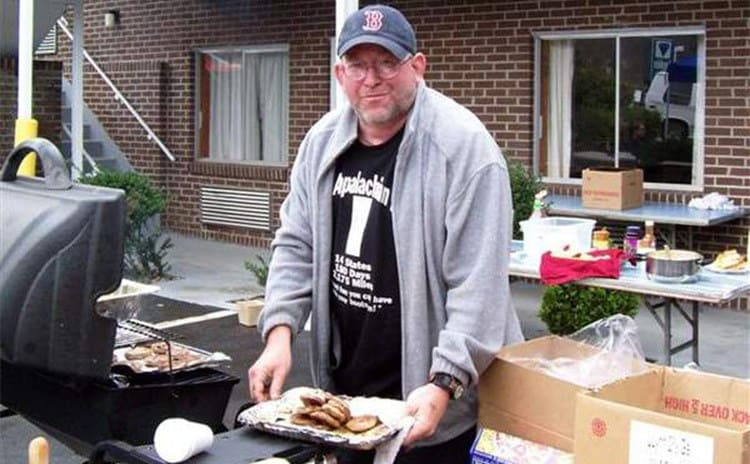 Baltimore Jack standing in front of a grill with a plate of food