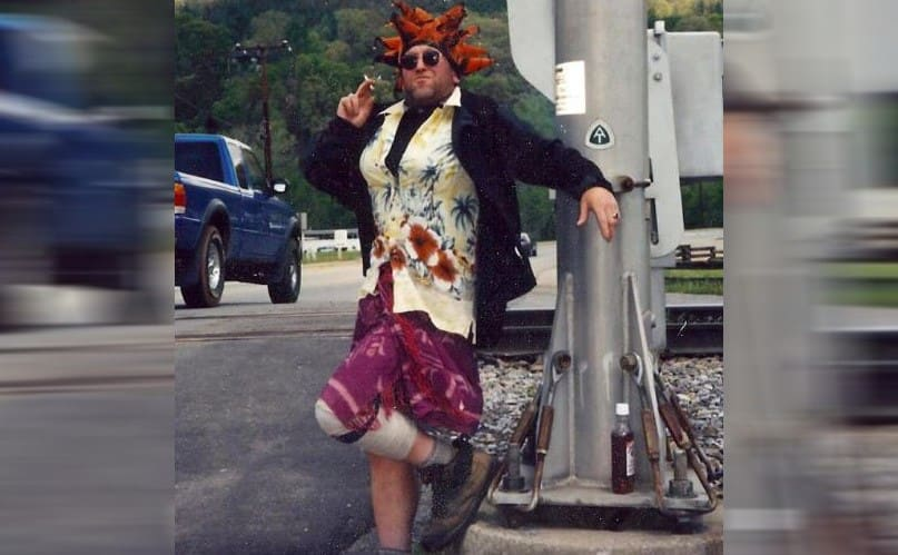 Baltimore Jack dressed up in funny clothing posing near a railroad track