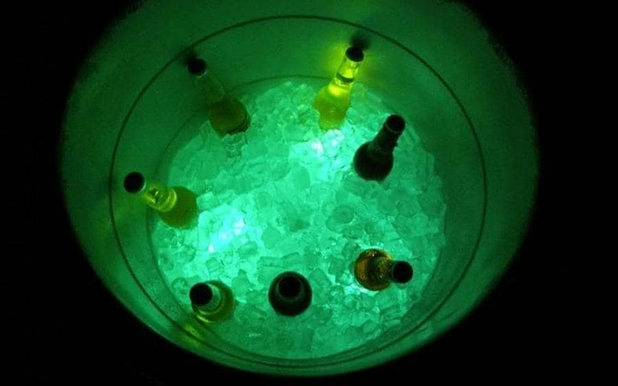 A Cooler box filled with ice and drinks, glowing from a neon stick