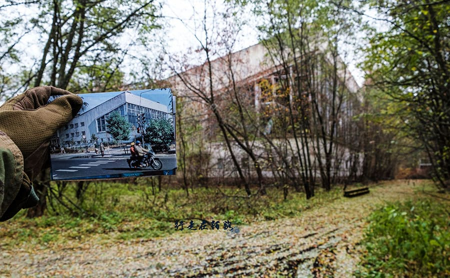 An abandoned pool with a photograph held in front of the abandoned building of what it looked like before the disaster