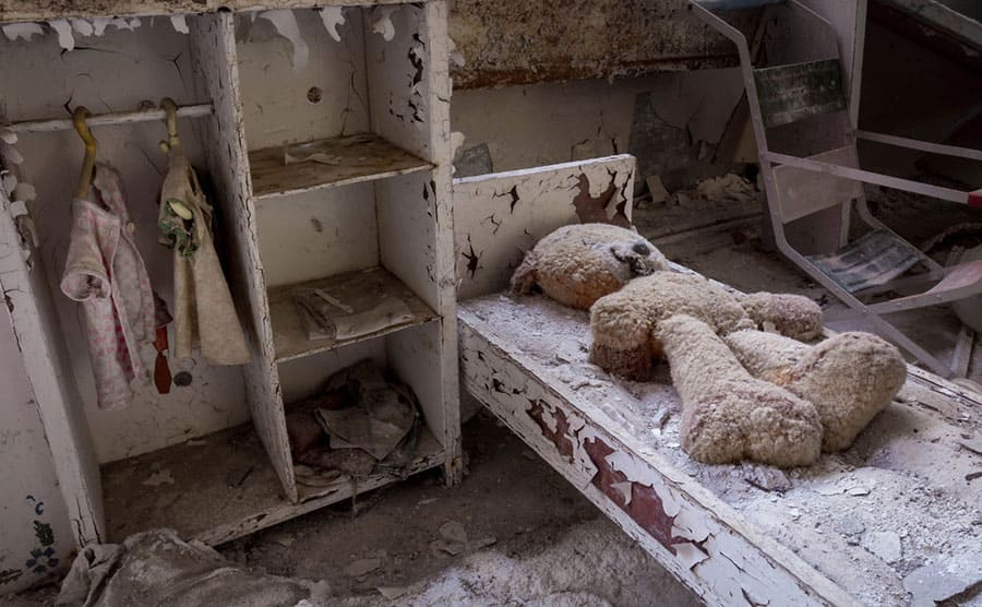 A doll and clothing sitting around an abandoned room