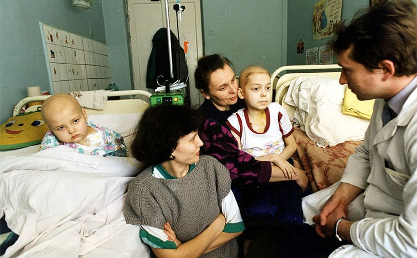 A doctor talking to two women with their children in the hospital after the disaster