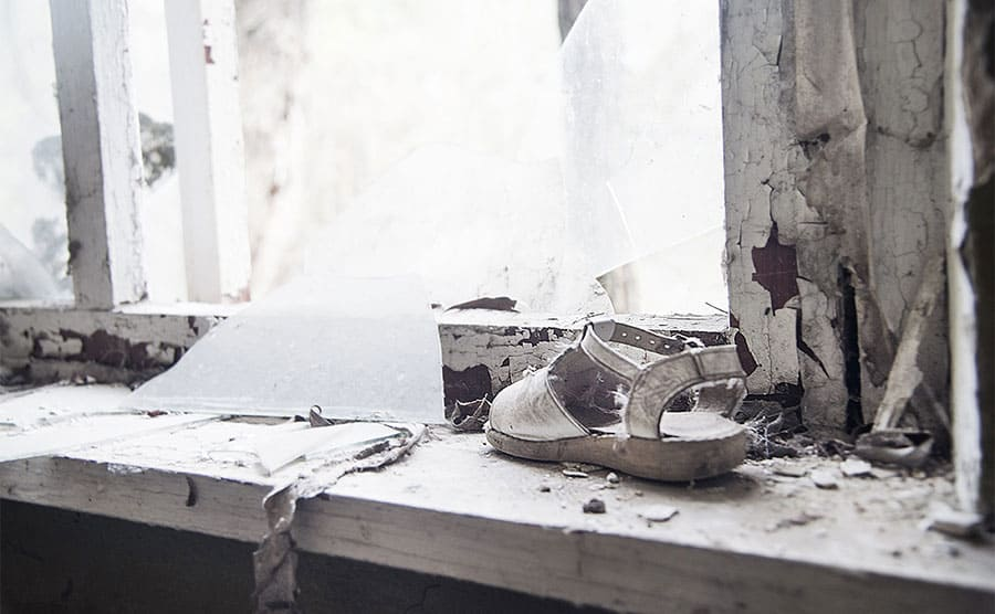 A single shoe sitting on the windowsill in an abandoned building