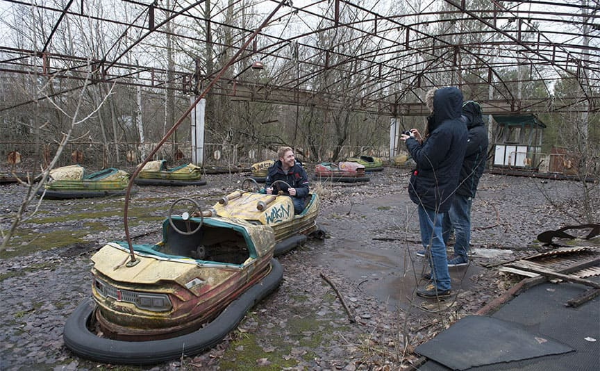 Tourists taking photographs in the abandoned bumper cars in Pripyat