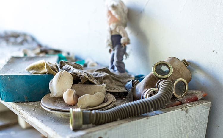 Gas mask and a doll sitting in an abandoned school