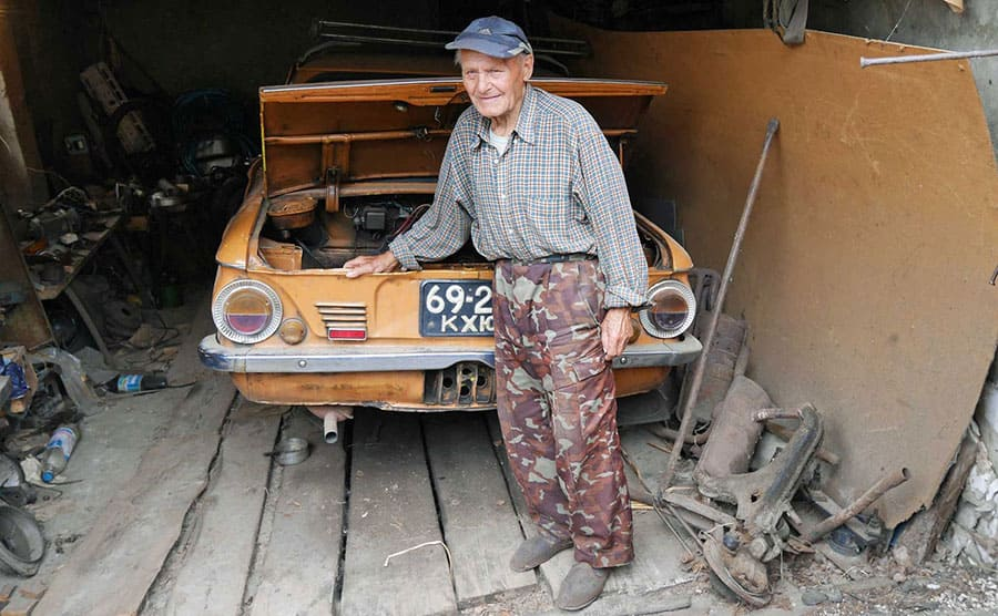 Ivan Semenyuk standing next to an old car with the hood up in a garage