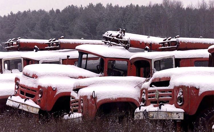 Vehicles covered in snow sitting in the woods