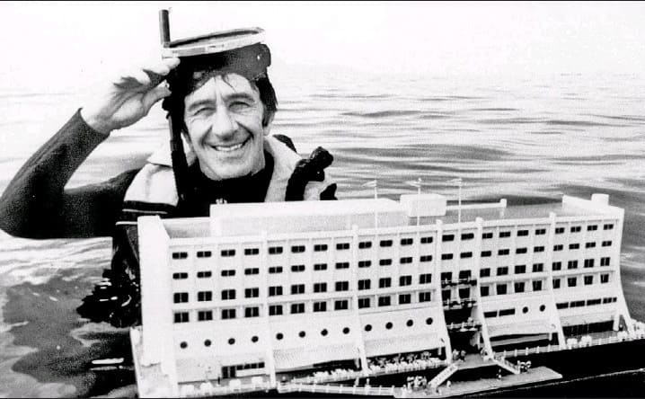 Doug Tarca next to a model of the floating hotel
