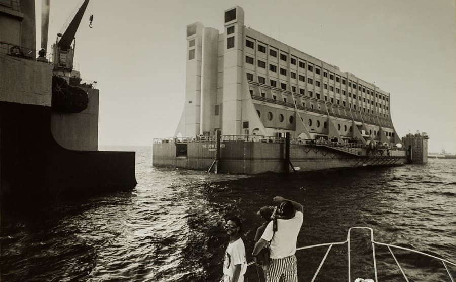 The John Brewer Floating hotel with people in a smaller boat taking photographs