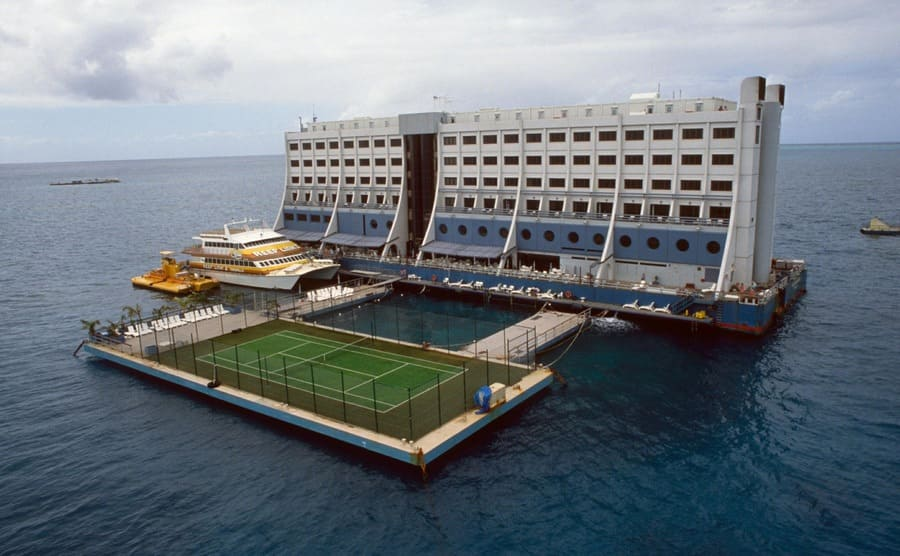 The floating hotel with a view of the tennis course and the yacht attached to it