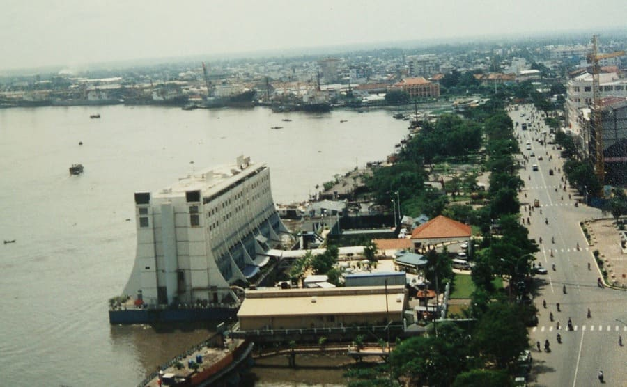 A photograph of the floating hotel docked against the Saigon shoreline