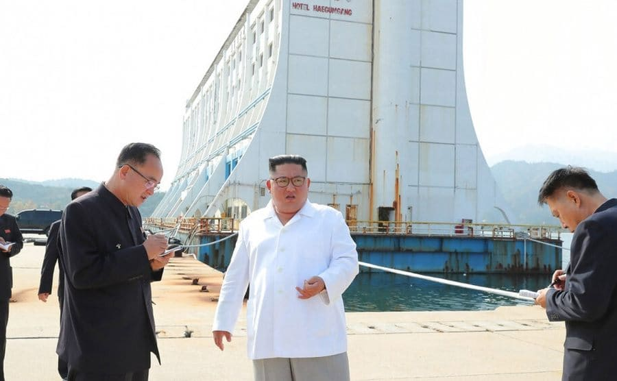 Kim Jong Un and his staff standing and talking in front of the run-down Hotel Haegumgang