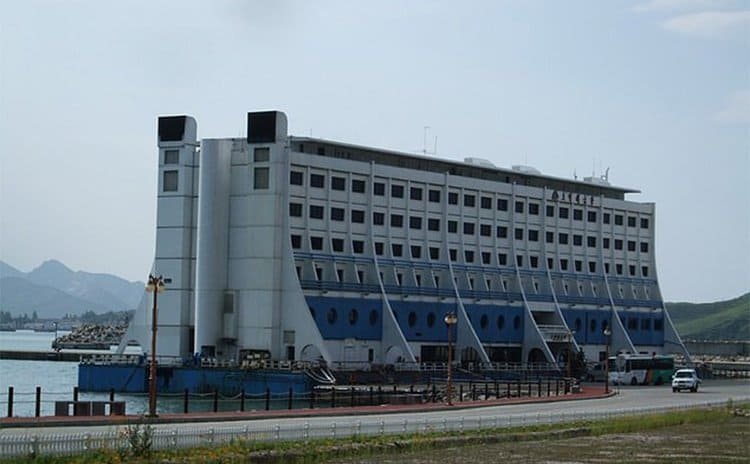 The floating hotel docked next to a parking lot