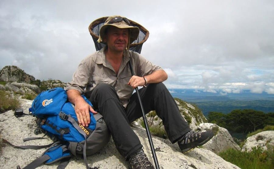 Julian Bayliss sitting on a rock resting while on a hike