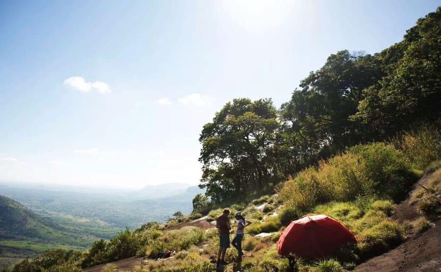 A view from the top of Mount Lico with a man and woman standing by a pitched tent