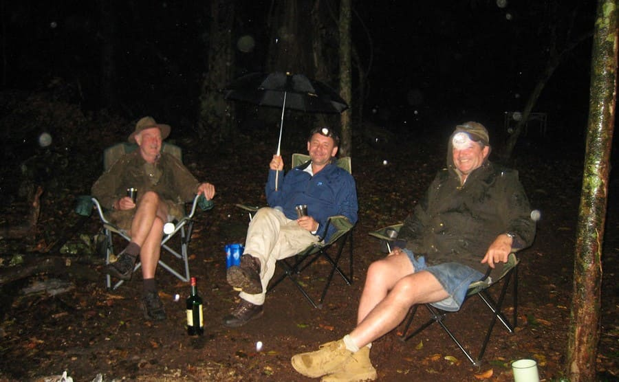 Colin, Julian, and Steve sitting in outdoor chairs at night in a light drizzle