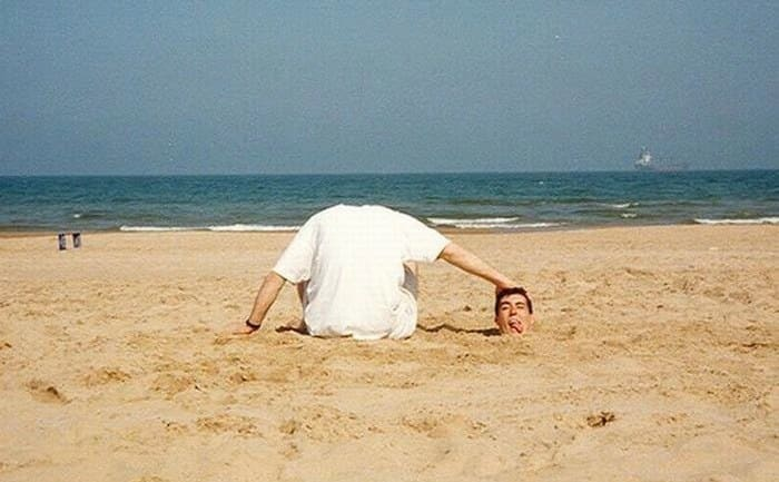 A man buried in the sand up to his head while his friend sits next to him with his head out of view