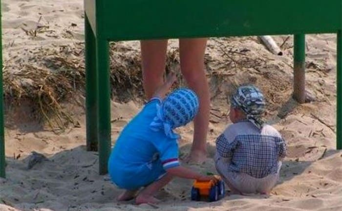 Two young boys pointing from underneath a dressing room at the beach, insinuating that they are looking up a woman's bathing suit