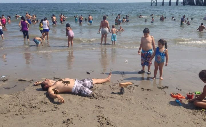 A man lying in the sand with his right leg buried in the sand up to his knee and a fake foot sticking out of the sand in front of him
