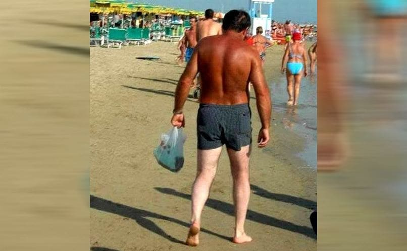 A man with a tan upper half of his body and very white legs