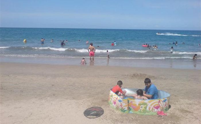 Kids sitting in a small pool on the shore of the ocean