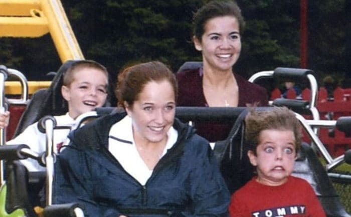 Four younger people on a roller coaster with one of the kids looking very scared