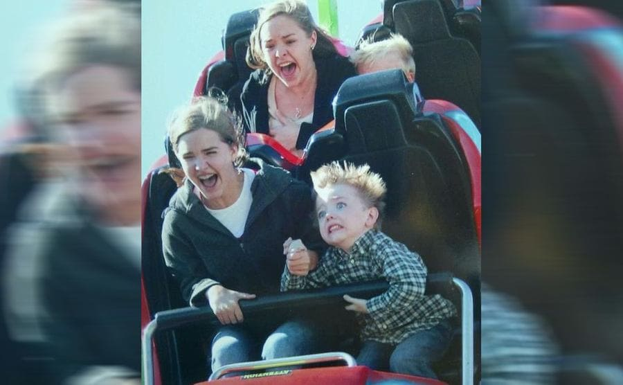 Kids on a roller coaster with a small boy in the front looking very scared