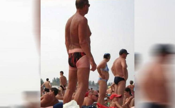 A man standing on the beach wearing a speedo with a tan line for shorts