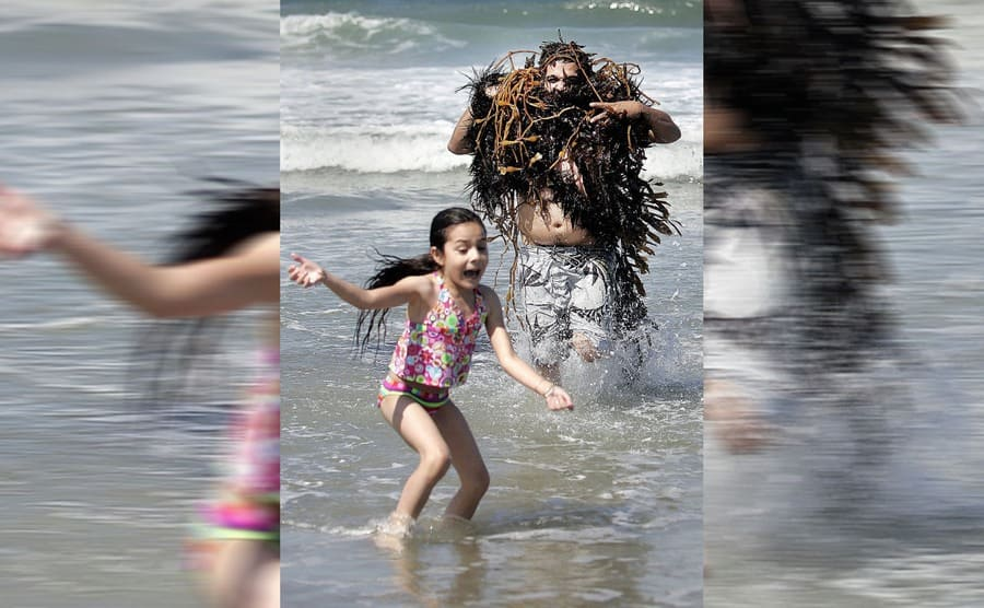 A girl screaming and running away from a man with a bunch of seaweed hanging from him