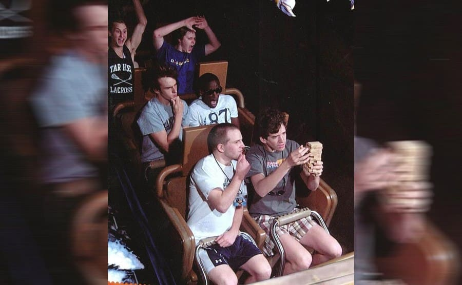 College guys on a roller coaster while the two in the front seat play Jenga