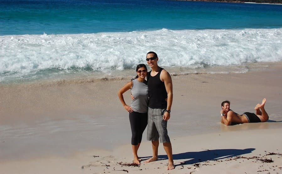 A couple taking a photograph in front of the shore with a man posing behind them