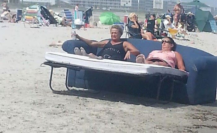 An older couple sitting on a couch bed at the beach