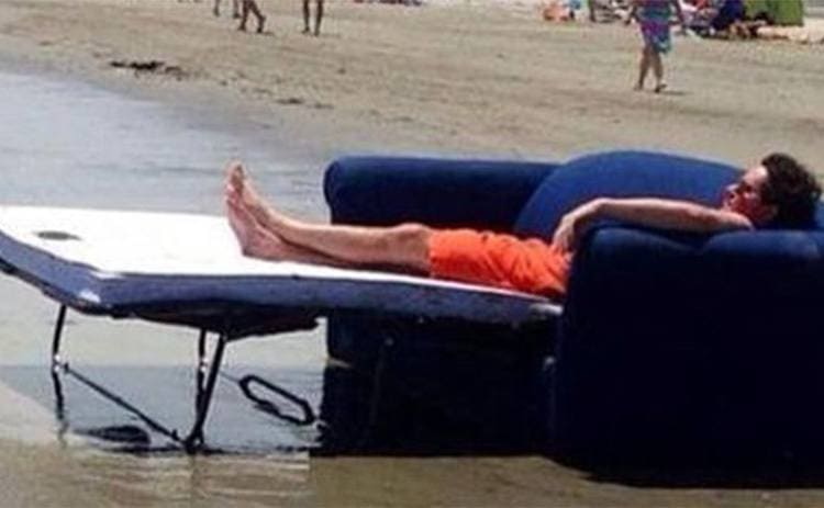 A man sitting on a couch bed at the edge of the water at the beach