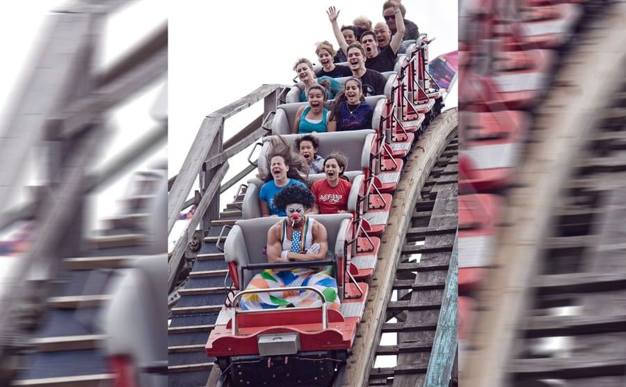 A roller coaster car full of people and a sad clown in the front seat